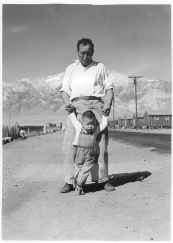 Manzanar, Calif.--Grandfather of Japanese ancestry teaching his little grandson to walk at this War Relocation Authority center for evacuees. Photographer: Lange, Dorothea Manzanar, California