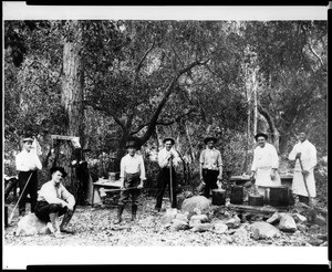 Sunset Club camp cooks posing with cooking utensils, ca.1910