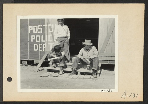 Poston, Ariz.--Members of the police department carving clubs at this War Relocation Authority center for evacuees of Japanese ancestry. (L to R) standing: Chief Kiyoshi Shigekawa; Toshio Ikeda and Hitoshi Nitta. Photographer: Clark, Fred Poston, Arizona