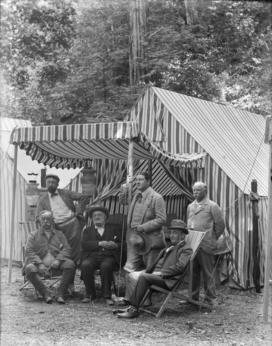 Group portrait of six men in front of striped tent, Bohemian Grove. [negative]