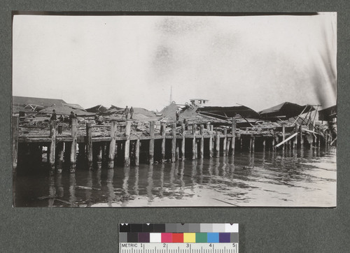 [Collapsed structures atop pier. Unidentified location.]