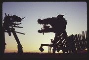 AUG77P9-34: dragons fighting sculpture, sunset