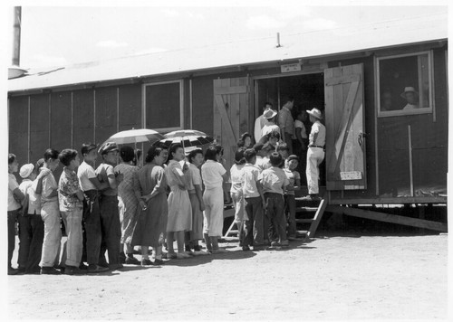 Part of a line waiting for lunch outside the mess hall at noon. Photographer: Lange, Dorothea Manzanar, California