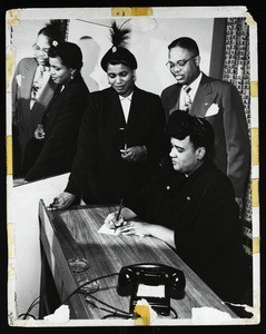 Unidentified woman signing at a desk as an unidentified couple look on, COGIC