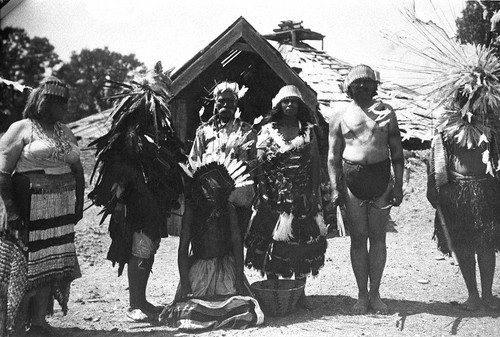 Laura Burrows, Mike Jefferson, James Brown, Georgina Joe Smith, George Scott, and Pedro Wright dressed in dance regalia in front of round house