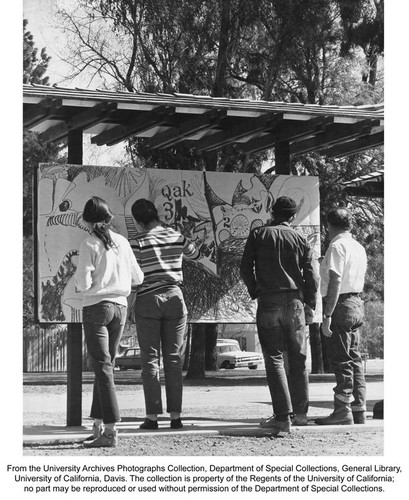 Art, Four people facing an outdoor sign board. Two are drawing on the board