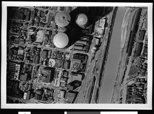 Aerial view of a river passing near storage tanks in Los Angeles County, 1938