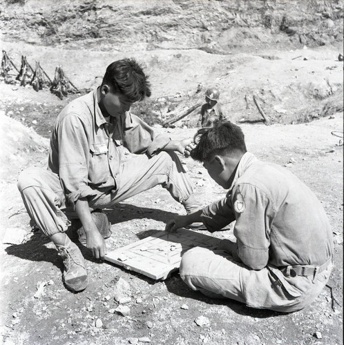 Two South Korean soldiers playing yut nori