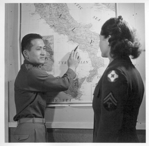 1st Lt. Shigeru Tsubota points out where he was serving in Italy with the 100th Battalion to a WAC corporal. Lt. Tsubota is at the Moore General Hospital recovering from a leg wound received in action overseas. Photographer: Van Tassel, Gretchen Swannanoa, North Carolina