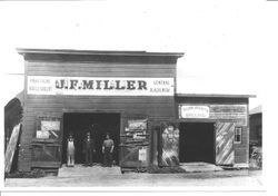 Three men in the entrance to J. F. Miller blacksmith shop in Sebastopol, about 1880s to 1890s