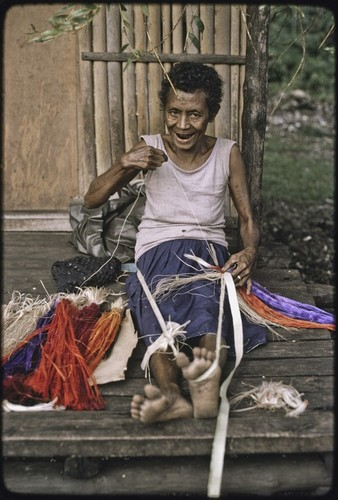 Weaving: smiling woman attaches dyed banana fibers to a cord wrapped around her foot, creating a colorful skirt