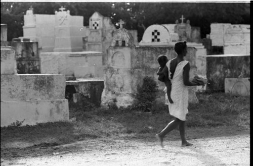 Woman with child walks in front of a cemetery, San Basilio de Palenque, 1975