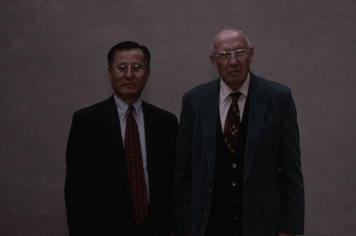 Peter Drucker stands next to an individual