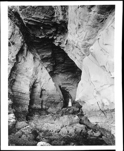 Woman standing in Mamoth Cave at Point Loma in La Jolla, ca.1905