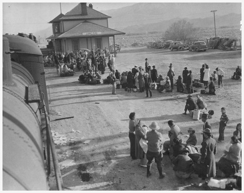 Evacuees of Japanese ancestry waiting to board buses which will take them to the War Relocation Authority center at Manzanar where they will spend the duration. Photographer: Albers, Clem Lone Pine, California