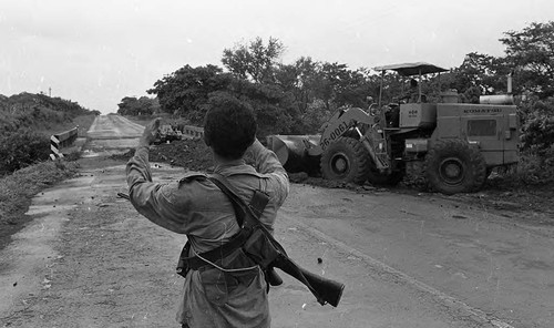 Man looks towards a tractor on a bridge, Nicaragua, 1979