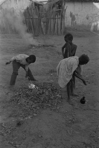 Children playing with a small fire in the street, San Basilio de Palenque, ca. 1978