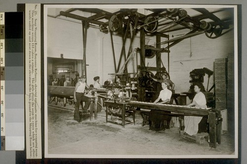 Soap Wrapping Room, Bayonne Refinery, showing automatic machine for wrapping soap. This machine wraps 115 cakes a minute. The girls place the soap in cases which are afterwards nailed up and sent down in the elevator in the background to the Shipping Room below