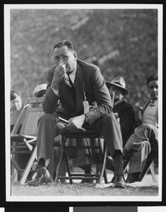 University of Southern California head football coach Jeff Cravath at the UCLA-USC game, sitting in a wooden chair on the sidelines blowing his nose, Los Angeles Coliseum, 1944