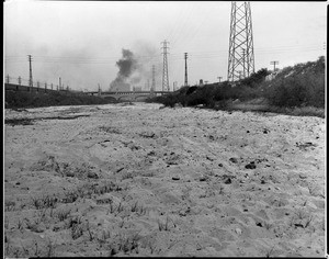 View of the bed of the Los Angeles River near Seventh Street, showing a bridge in the background