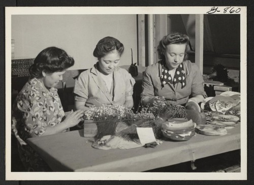 These three women, two of them Issei resettlers, are assembling artificial flower novelties in a workroom of the Miya Flower