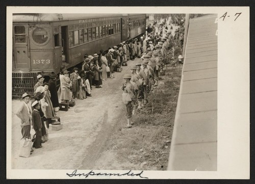 Persons of Japanese ancestry arrive at the Santa Anita Assembly Center from San Pedro, California. Evacuees lived at this center at the Santa Anita race track before being moved inland to relocation centers. Photographer: Albers, Clem Arcadia, California