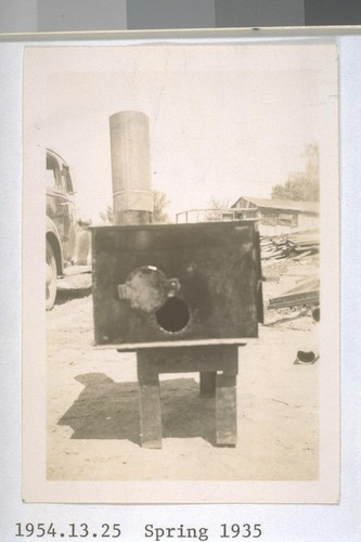 Spring, 1935, Hooverville, Kern County. On highway north of Bakersfield. Hand made camp stove, made by a stranded worker out of sheet iron gathered from automobile bodies found in the city dump. Contains a grate, oven and door latch. Sold at $3.50. Kept this man off relief