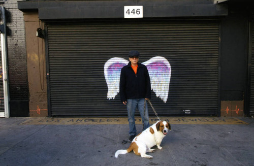 Stuart Rapeport and dog posing in front of a mural depicting angel wings
