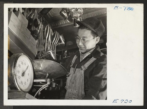 Joe Sitsuda weighs nails for a customer in the Union Hardware Store in Denver. Joe, a former Los Angeles vegetable
