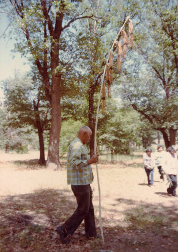 Unidentified man holding the Maple Bark Flag at the Greenville Bear Dance--1983