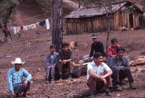 Guatemalan refugees sitting on logs outside of their huts, Santiago el Vértice, ca. 1983