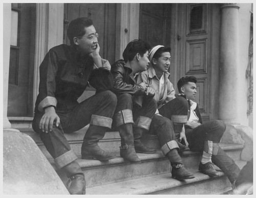 High school boys look over Buchanan Street scene, prior to evacuation of residents of Japanese ancestry. Evacuees of Japanese ancestry will be housed in War Relocation Authority centers for the duration. Photographer: Lange, Dorothea San Francisco, California
