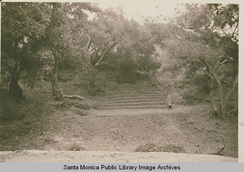 Young woman walking in an informal amphitheater at the Assembly Camp, with oaks and sycamores shading the setting, Temescal Canyon, Calif