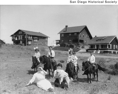 Children on ponies and two women with a dog in front of houses