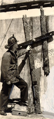 [Fireman inspecting a ladder that was burned in a fire on the cantilever span of the San Francisco-Oakland Bay Bridge]