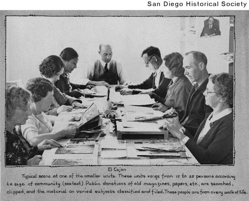 Group of people seated around a table clipping articles for the Works Progress Administration