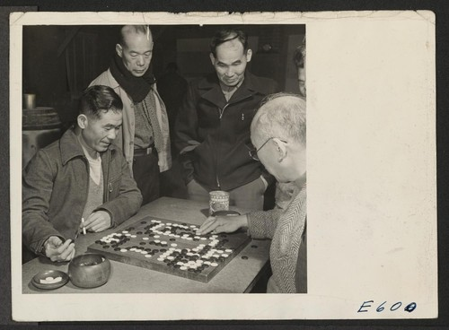 A group of centerites gather around two of the center's expert Go players. The game, popularly conceived as a game