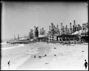 Children playing on the beach in front of an oil field, Playa del Rey
