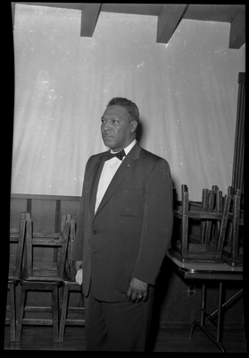 Portrait of man in bow tie standing next to chairs