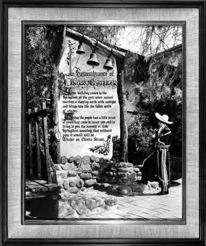 A photogrpah of a man standing on Olvera Street, reading a poster in Remembrance of Harry Chandler