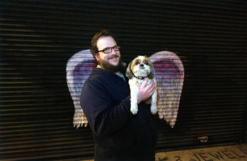 Jim Winstead and Wonton posing in front of a mural depicting angel wings