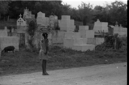 Woman with a bowl full of fish walks along a cemetery, San Basilio de Palenque, 1975