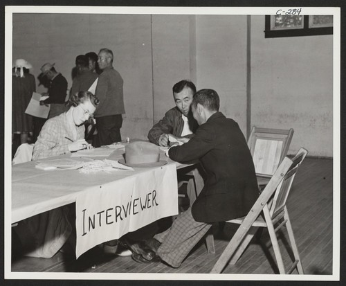 Father and son give pre-evacuation data at Wartime Civil Control Administration station. Evacuees of Japanese ancestry will be housed in War Relocation Authority centers for the duration. Lodi, California
