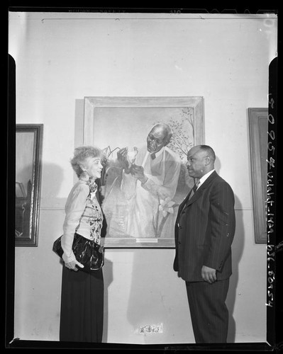 Artist Betsy Graves Reyneau and AACP president Thomas L. Griffith standing besides portrait of Dr. George Washington Carver, 1948