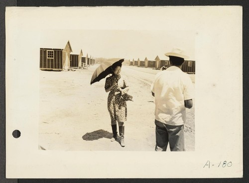 Poston, Ariz.--(Site #1)--This evacuee is fortified with an umbrella for protection from the sun, and high-top boots for strolling through the dusty streets at this War Relocation Authority center. Photographer: Clark, Fred Poston, Arizona