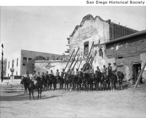 Soldiers on horseback in front of the Mission San Diego de Alcala