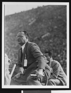 University of Southern California head football coach Jeff Cravath at the UCLA-USC game, sitting in a wooden chair on the sidelines yelling, Los Angeles Coliseum, 1944