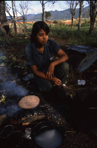 A female Contra soldier cooks food for the camp, Nicaragua, 1983