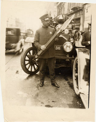 [Officer Nelson J. Mathewson examining part of window sill in front of a Fire Department car]
