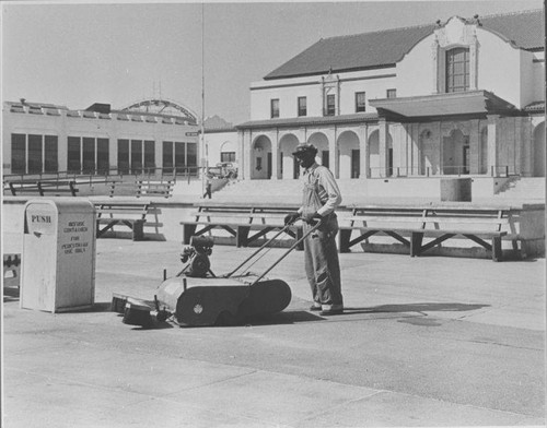 Santa Monica City worker operates a mechanical sweeper in front of the Ocean Park Municipal Auditorium